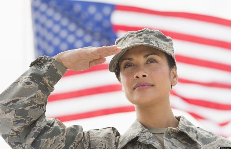 USA, New Jersey, Jersey City, Female army soldier saluting, American flag in background
