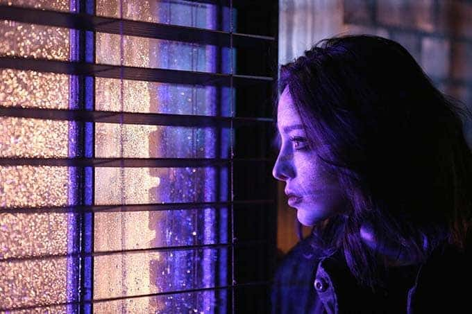 Emma Dumont as Polaris peers pensively through a window at night in Fox's THE GIFTED.