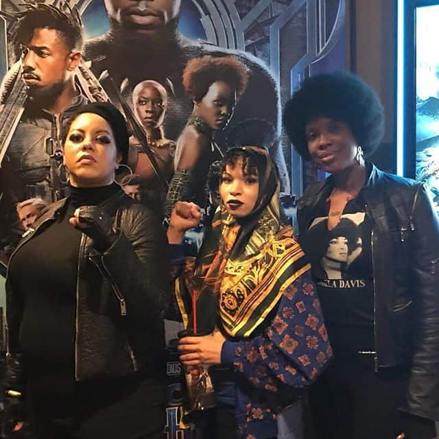 Author Blair Imani poses with others in African inspired and Black Panther Party costumes