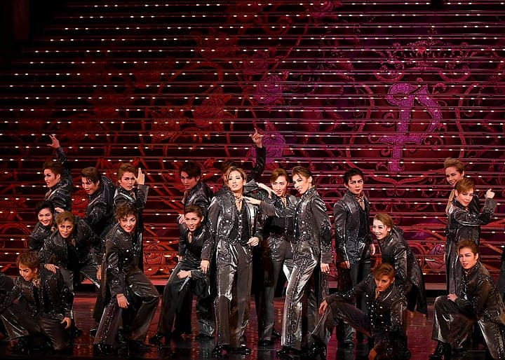 The players pose dramatically in black leather suits