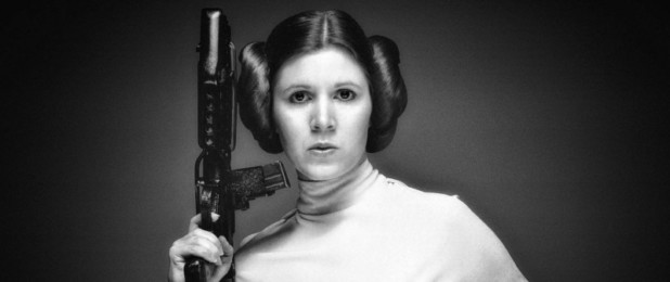 Carrie Fischer as Princess Leia Poses with a blaster in a black and white vignette photo.