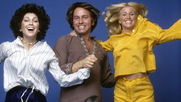 Three's Company cast is jumping while holding hands. left to right: Janet, Jack, and Chrissy.