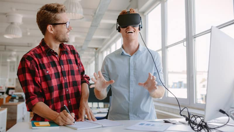 Shot of two young men testing virtual reality glasses in office. Businessman wearing VR goggles and colleague writing notes.