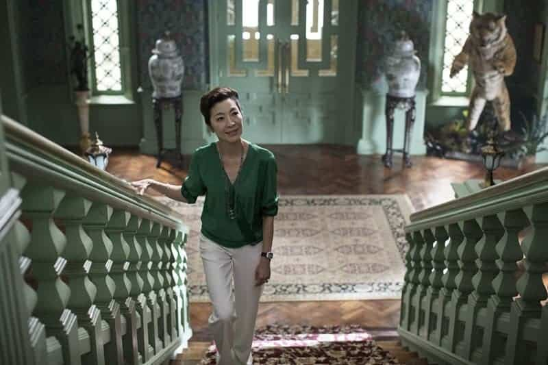 Michelle Yeoh as Eleanor Young on the staircase at Tyserall Park in Crazy Rich Asians