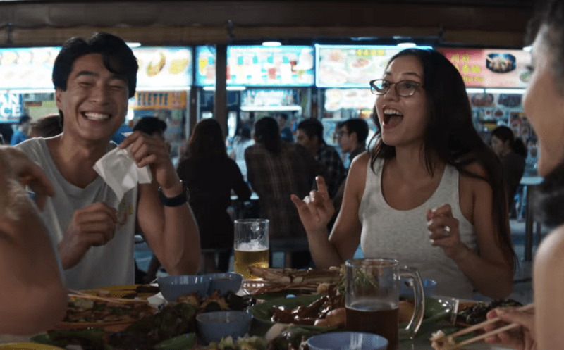 Colin Koo and Araminta Lee laughing of chicken satay in Crazy Rich Asians.