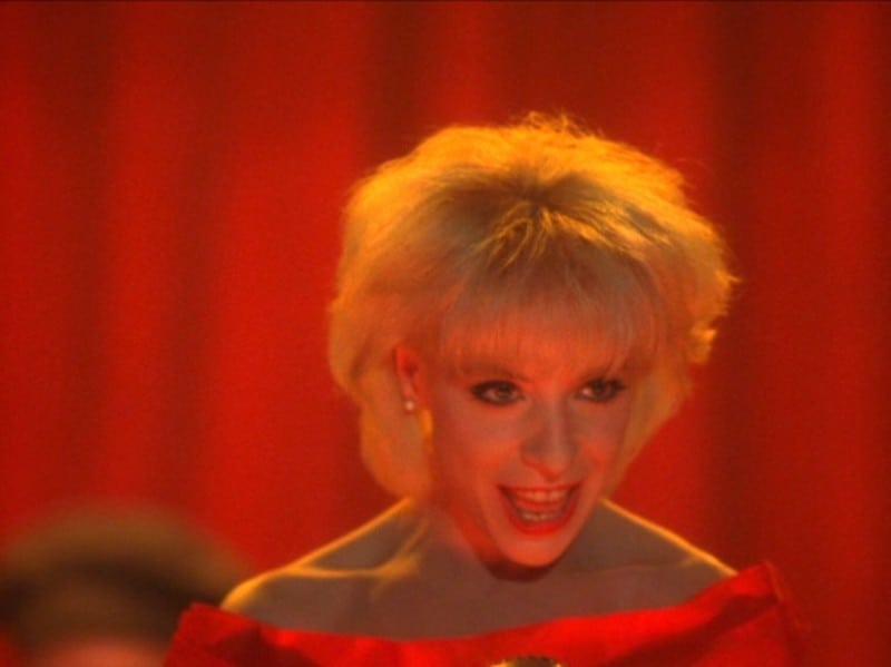 Julee Cruise in Twin Peaks wearing a red dress against a red curtain singing