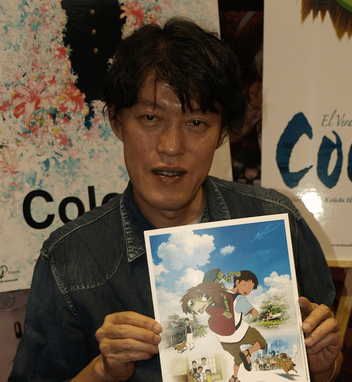 Keiichi Hara holding up an autographed poster for SUMMER DAYS WITH COO.