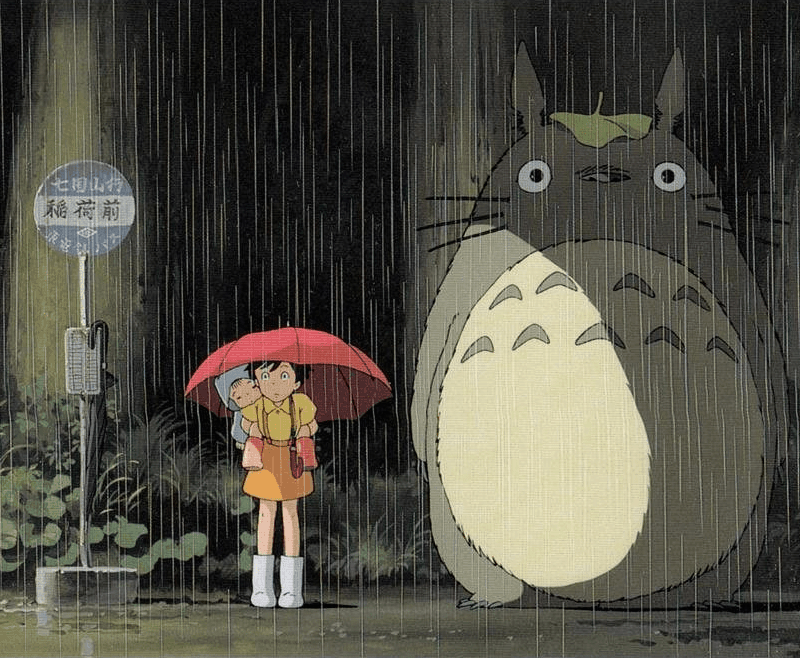 Satsuki and Mei stand at the bus stop with Totoro in the famous scene from MY NEIGHBOR TOTORO.
