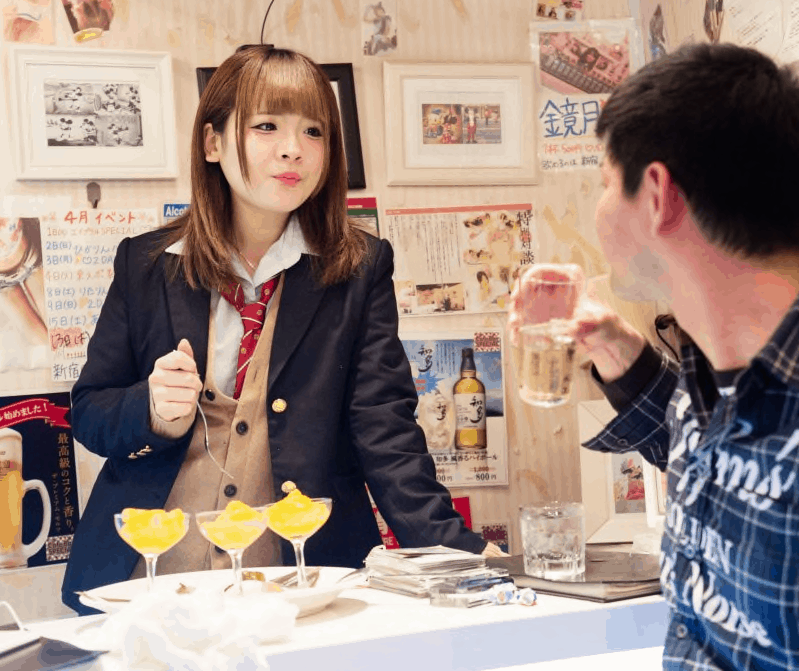 An 18-year-old waitress in a Japanese cafe speaking with a guest over three glasses of sherbet.
