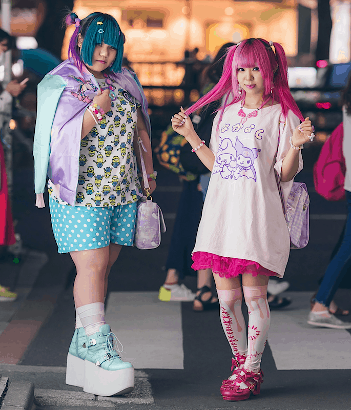 Two girls dressed in kawaii fashion in Harajuku, Tokyo, at night.