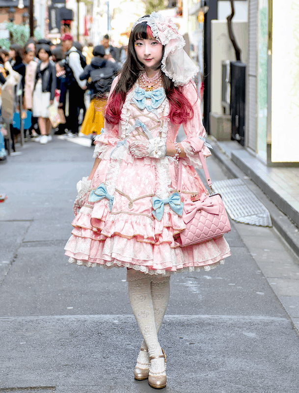 A Harajuku street. Famous Youtuber and Lolita fashion model RinRin Doll stands in the center.